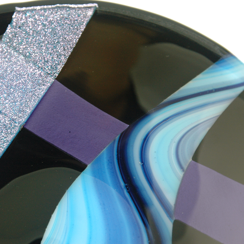 Dichroic Glass with blue swirls on black background
