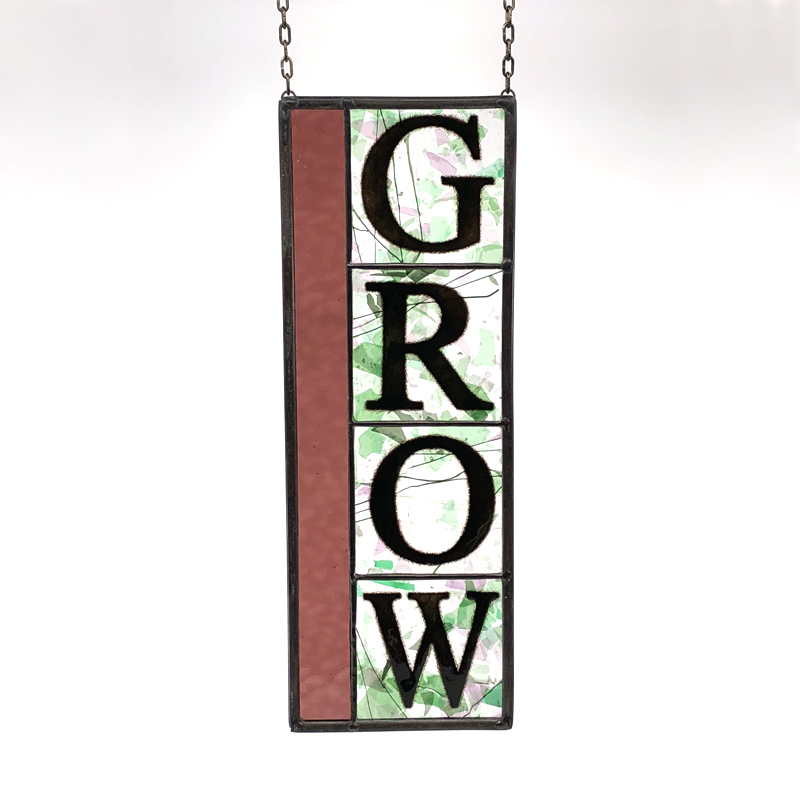 Stained glass with block letters spelling GROW