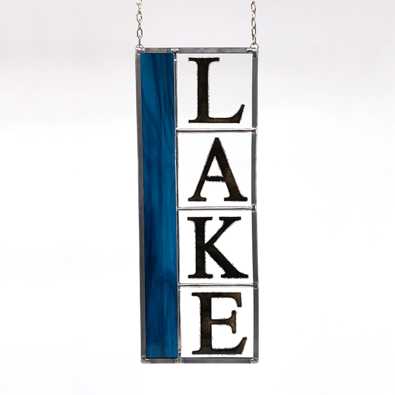 Stained glass with block letters spelling LAKE
