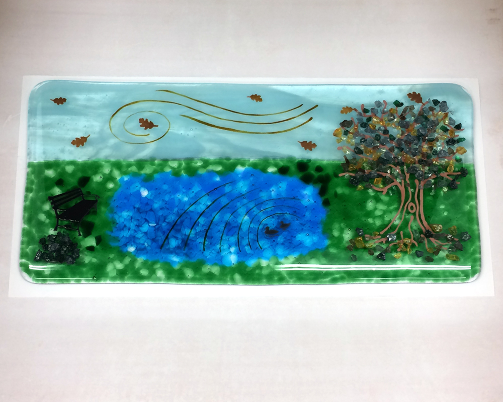 Custom pond plate with oak tree and bench with leaves blowing in wind