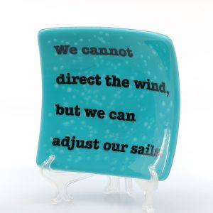 Teal plate with quote We Cannot Direct The Wind, But We Can Adjust Our Sails.