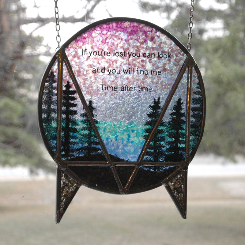Round stained glass of lake with evergreens