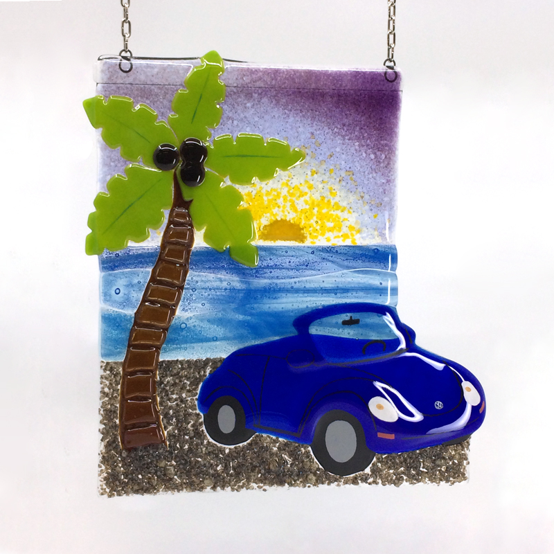 VW Bug on a beach with palm tree and sunset