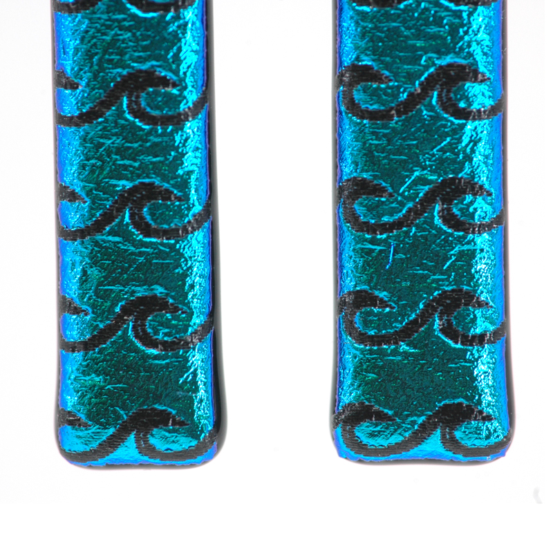Closeup of bright sparkly aqua blue glass earrings with black waves
