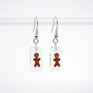 Gingerbread man with yellow icing painted on clear fused glass earrings