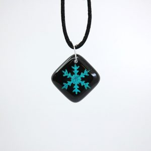 Blue snowflake on black fused glass