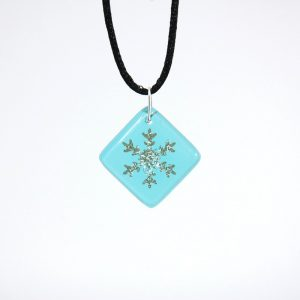 Snowflake on light blue fused glass