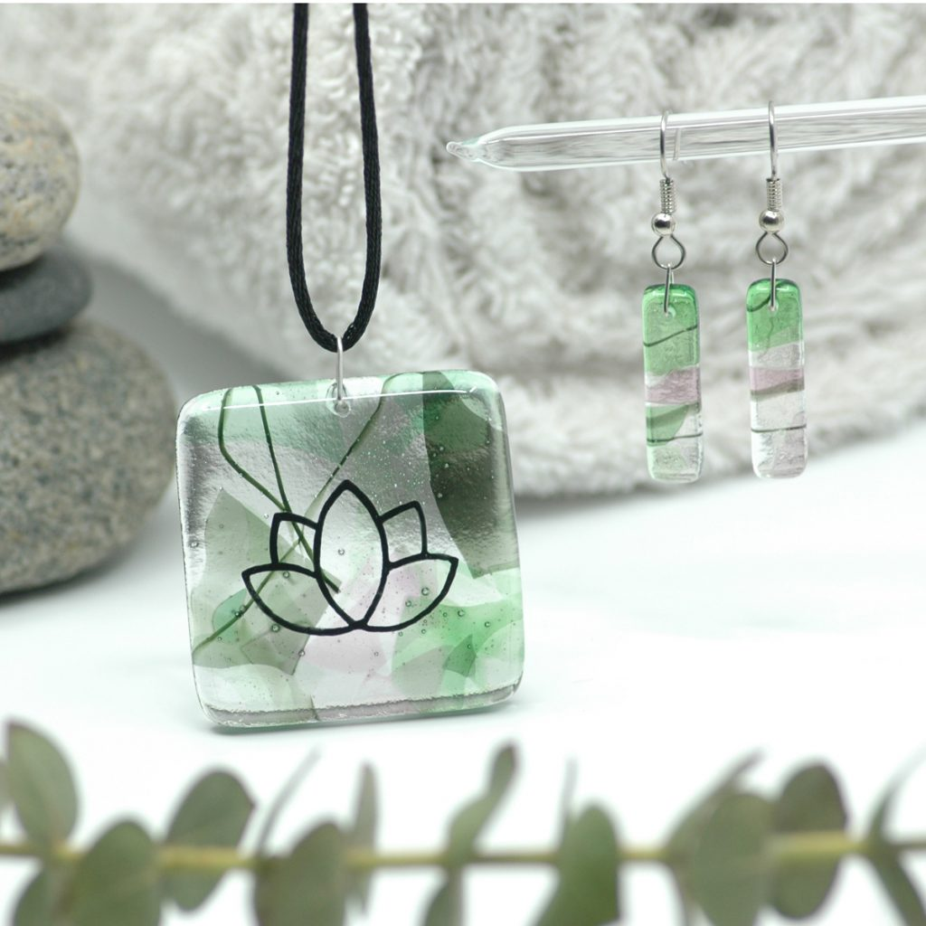 Fused Glass Gaia Lotus Pendant and Gaia Earrings with river rocks, spa towel, and branch